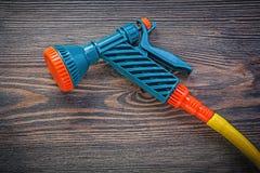 Water sprayer garden hose on wooden board agriculture concept.  royalty free stock photos