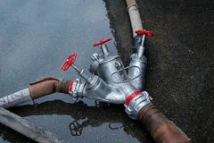 Fire hose and tee for water on the ground stock photos