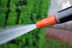 Water spraying from a garden hose. To water a lawn. To water a grass on a lawn stock image