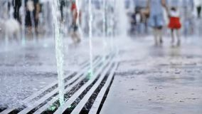 Water sprays of a floor fountain close up and a woman with a child running away enjoying life. Slow motion shot of water sprays of a Moscow floor fountain and stock video footage