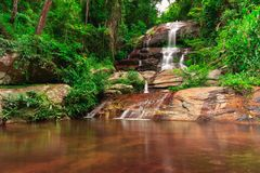 Water spring reflection from rocky jungle waterfall. stock image