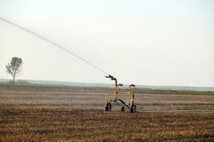 Preparation of the field for cultivation.Water sprinkler installation in a field during the drought stock image