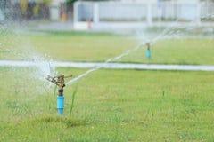 Water sprinkler spray watering in park. Stock Image
