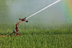 Water sprinkler system irrigating a farm field Royalty Free Stock Photos