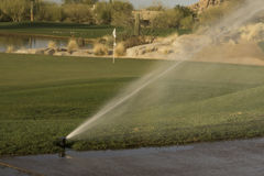 Water sprinkler use on golf course Stock Photos