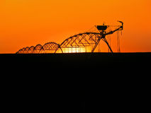 Water Sprinklers. Silhouetted in prarie lands, sunset in background royalty free stock images