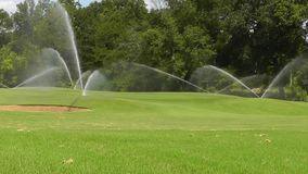Water Sprinklers Dance Across Golf Course Greens stock video footage