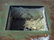 Water Square. Rippling water inside a rusting metal square stock photo