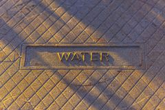 Water stamped on a man hole cover stock photography
