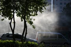 Water steam in sunlight on a street with cars in Urumqi, Xinjiang, China stock image