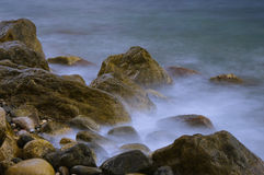 Water and stones. Yellow stones in the sea Stock Photography