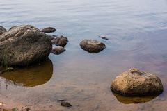 The shore of the lake. The water and the stones Stock Images