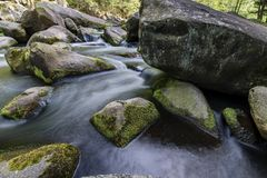 Water and stones. Wild water running between granite stones Royalty Free Stock Images