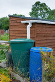 Water storage barrel with garden shed. Water barrels attached to garden shed Royalty Free Stock Image