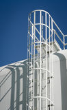 Water Storage Tank Ladder. The morning sun casts the shadow of  a metal ladder of a steel water storage tank Stock Photos