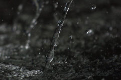 Water stream the air in dark. Splashing water fly in the air. Part of the drops is in focus, part - out of the focus. Royalty Free Stock Image