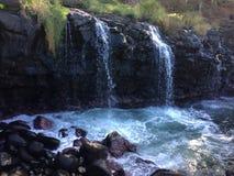 Water Stream Entering Pacific Ocean near Queen`s Bath in Princeville on Kauai Island, Hawaii. Royalty Free Stock Photo