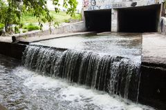 Water stream flowing out the underground tunnel Stock Images