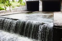 Water stream flowing out the underground tunnel Royalty Free Stock Image