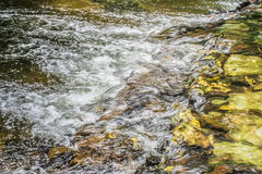 Water stream flowing past rock and stones in the river. HDR filter effect Stock Images