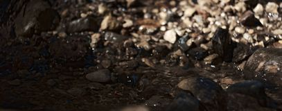 Water stream flowing through rocks with rocks in background stock photo