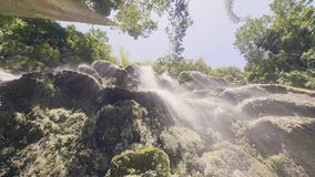 Water stream flowing on rocky cliff in tropical forest view from bottom. Flowing water of tropical waterfall in.  stock video