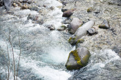 Water of stream flows through between the stones Stock Photo