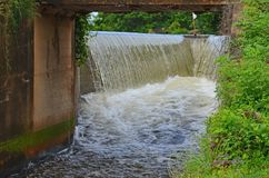 Water from side channel spillway through the tunnel. Water stream from two side channel spillway through the tunnel of the road Royalty Free Stock Image