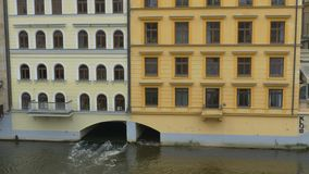 Water Channel under Building. Water stream under building flowing on a channel stock footage