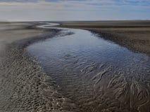 Water streams over sandy beach to the ocean Royalty Free Stock Photos