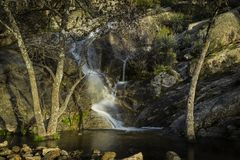 Water streams, rocks, trees and beatiful sky. Through the mountains of the community of Madrid it is common to find currents of water that meander between rocks royalty free stock image