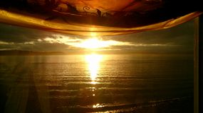 Water Sunset, through a curtained window Royalty Free Stock Photography