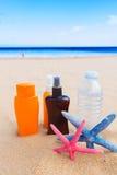 Water with suntun creams on sandy beach Stock Image