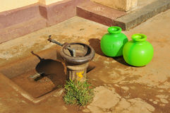 Water supply. Two plastic jugs brighten a village fountain in India ... water drops on the jugs Stock Photo