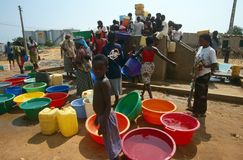 Water supply at a displaced peoples camp, Angola. People collecting water from a water supply at a displaced people's camp in Angola Royalty Free Stock Image