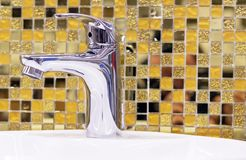 Water-supply faucet mixer on the background of yellow ceramic mosaic tiles.  stock photo
