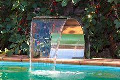 Water supply to the pool by a waterfall. Stock Photos