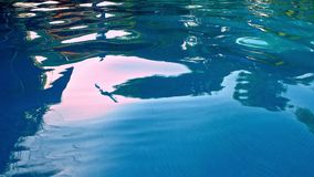 Water Surface Background. Stock footage features an extreme close-up shot of blue water in a swimming pool. The water is rippling in slow motion and has some stock video footage