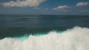 Water surface with big waves, aerial view.Bali. Aerial view of seascape with waves, ocean, large waves, sky with clouds. Surf, waves are crushing on coral reef stock video