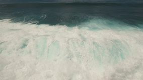 Water surface with big waves, aerial view.Bali. Aerial view of seascape with waves, ocean, large waves, sky with clouds. Surf, waves are crushing on coral reef stock video footage