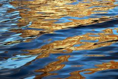 Water surface with bright orange reflections in cityscape stock image