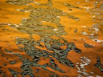 Water surface with colourful reflections. Water surface with colourful reflections mostly green and orange stock photo
