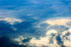 Water surface with deep blue clouds and sky reflection on it. Circle on water reflection of the sky in the evening, background, texture stock photo