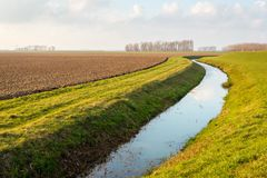 Water surface of a meandering ditch reflects the white clouds in. The blue sky. The field next to the ditch has recently been plowed in preparation for the new Royalty Free Stock Image