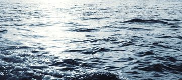 Water surface with ripples and sunlight reflections stock photos