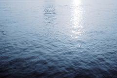 Water surface with ripples and sunlight reflections stock image