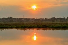 Water surface of river at sunset with reflection of orange sun. River landscape stock photography