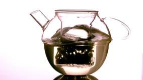Water swirling around loose tea in teapot stock video