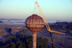 Water Tank Construction. The top half of a water storage tank is gently lowered into place on a misty morning stock photo