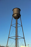 Water tank tower. Black metal water tank on a tower Royalty Free Stock Photos